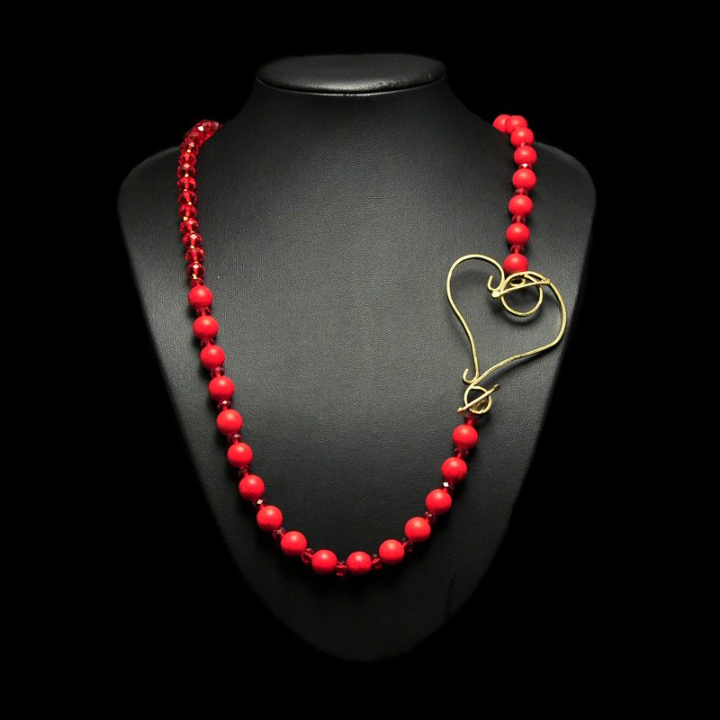 Handmade  necklace with coral  red crystals and a  heart with brass.